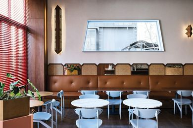 Brass accents, buttery caramel leather banquettes and the use of the Featherston Scape dining chair, an Australian mid-century classic, hint at 1950s Italian spaces.