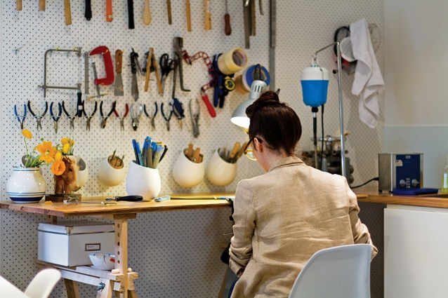 The jeweller at work in her secure studio, which features the low light levels needed for soldering.