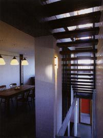 Ground floor, with the dining room to the left and slatted timber stair sandwiched between the thick brick walls. Image: Patrick Bingham-Hall.