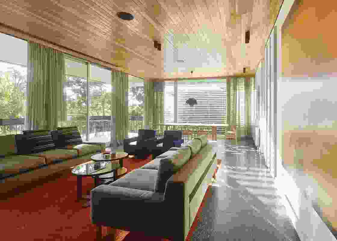 The living room ceiling is lined in a richly hued timber board, while a burnt orange carpet makes a bold statement.