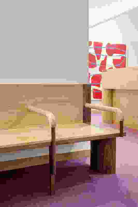 """The custom-made waiting lounge features """"fat and chunky"""" legs as a counterpoint to the fine and tapered furniture legs elsewhere in the practice. Artwork: Peter Atkins."""