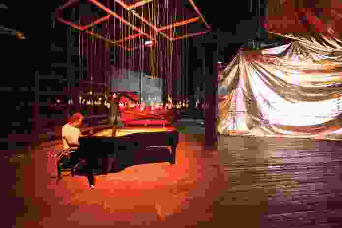 Composer/pianist Alister Spence playing the grand piano surrounded by pendants.