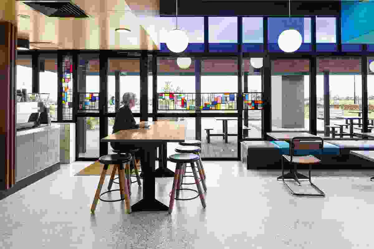 A cafe provides a communal area for the occupants, with interior and exterior seating.
