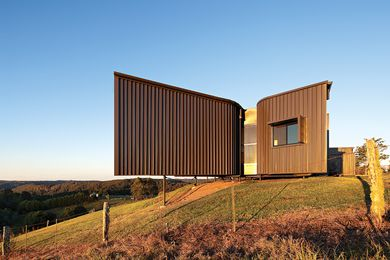 The earthy coloured, textured cladding blends into the hillside.