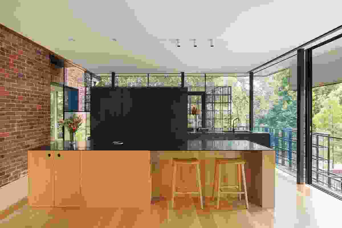 A wall of black-stained cabinetry lines the kitchen's western edge, affording it privacy from the neighbouring walkway.