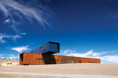 A Corten block is set athwart the hill, with the black upper floor sitting at a right angle across it.