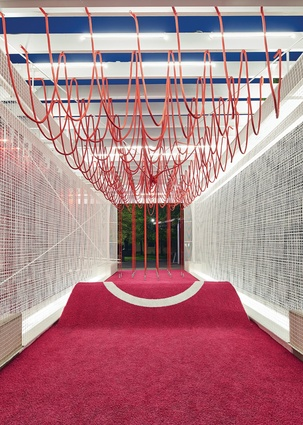 Netted walls and hanging ropes invite visitors to participate and engage with the pavilion.