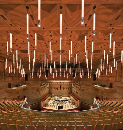 The auditorium's suspended tube lighting, like a sea of glowing batons, sustains the shining lights and embodied movement of the Hall's annular foyers.