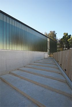 A series of steps along the east facade lead to a timber deck.