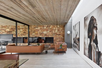 A stacked-stone feature wall provides a warm and textured backdrop to the living area, complemented by large-scale artworks. Artwork: Michael Peck.
