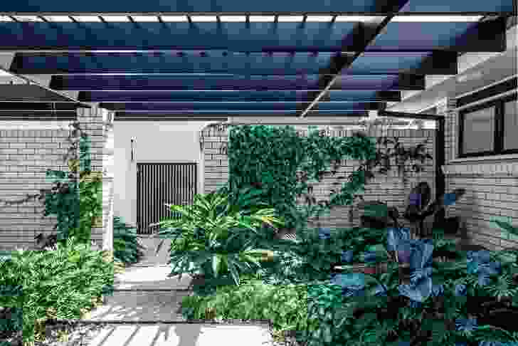 Bungalow Garden Rooms: The entry courtyard is a mix of shades of grey and green that highlights various foliage textures, with a ground layer of travertine pavers over sandstone river pebbles.
