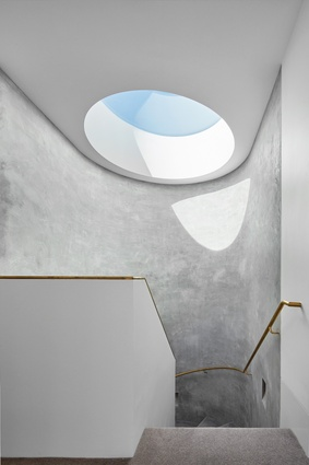 A dramatic circular skylight throws light onto the concrete wall of the spiral staircase.