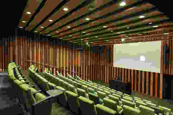 The vivid green and timber tones in the ground-floor theatre provide welcome respite from the stark white interior of the laboratories.