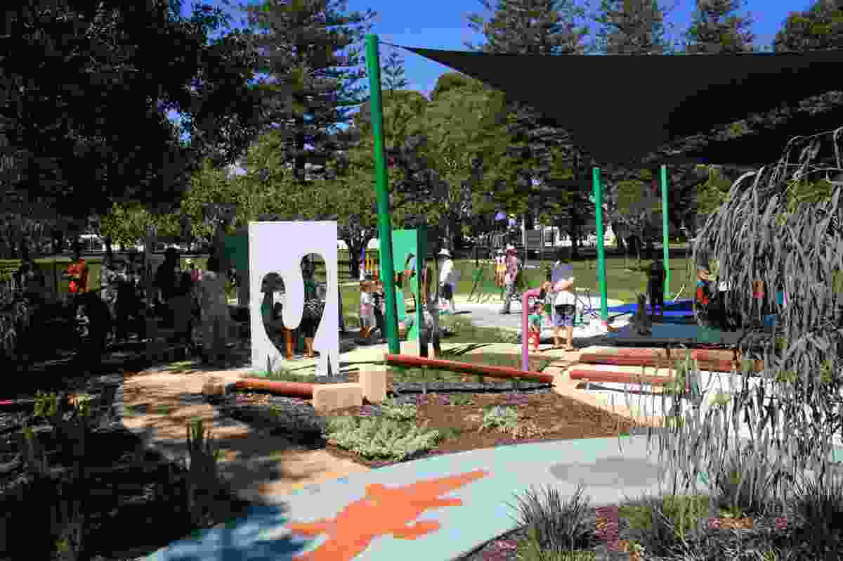 Parents and children explore the new playground at the opening day.