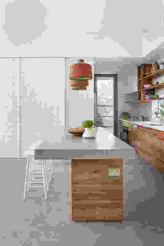 A white, pressed metal cupboard door adds another texture to the kitchen.