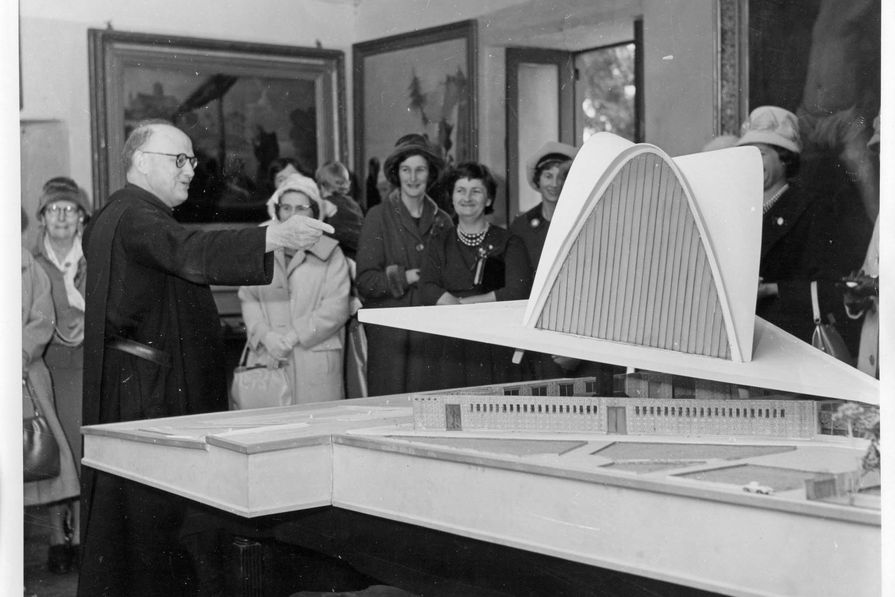 Fr Mauro Enjuanes showing the model of the cathedral to a group of local residents, c. 1959. Accession number 74893P.