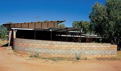 A windbreak wall curves around a ramp.
