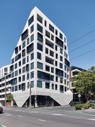The upper storeys of the monochromatic form fold and recede to acknowledge and not overshadow the adjacent dwellings.