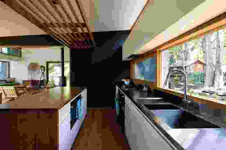A central kitchen bridges the living area and the bedroom wing.