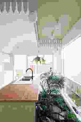 In a subversion of the suburban picket fence, pickets now hang from the kitchen ceiling, framing an interior garden below.