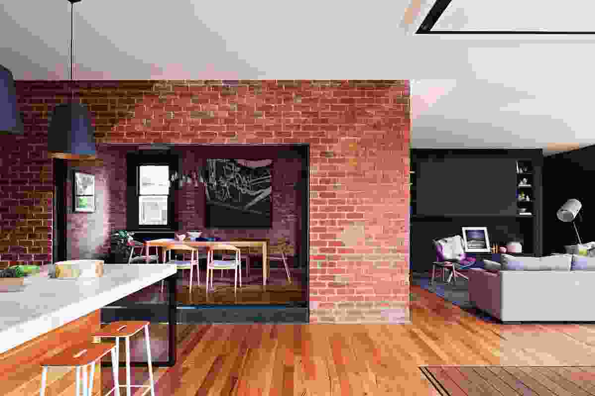 The dining room sits within the original red brick building envelope and is connected to the kitchen via a large opening. Artwork: Andrew Browne.