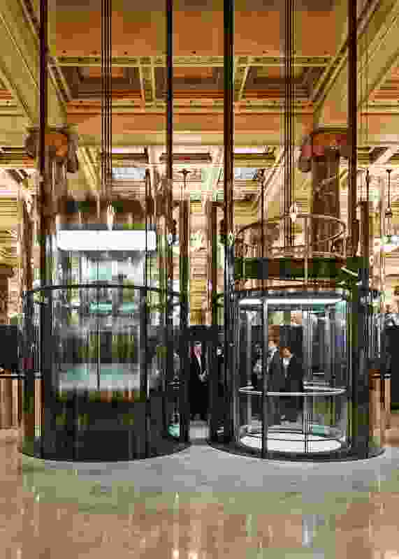 Two glass lifts shuttle visitors through the atrium to the roof-level reception spaces.