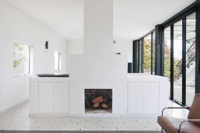The fireplace is housed in a white stepped form flanking the stair.