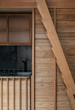 A timber box contains the kitchen, bathroom and laundry in the Kyoto Terrace House by Atelier Luke.