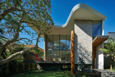 Otherwise rectilinear in form, the house features a curved roof and balcony that trace the canopy of a large jacaranda tree. Sculpture: Blaze Krstanoski-Blazeski.
