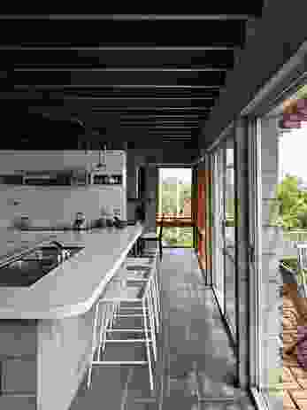 The kitchen is located along the northern edge of the house, open to an outdoor patio and the views beyond.