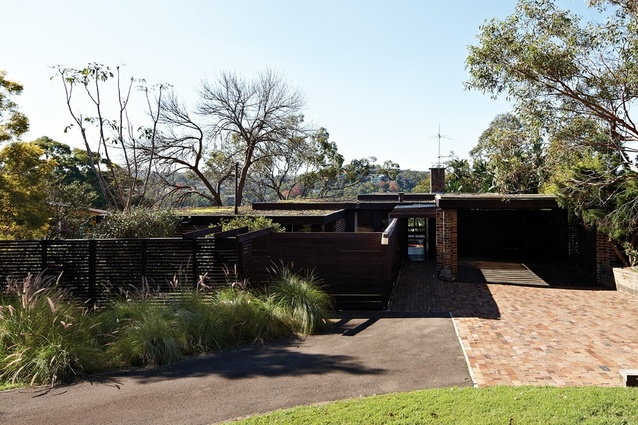 The house uses an organic pier structure to hold up three overlapping square roofs.