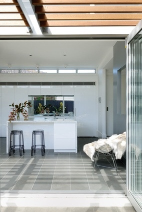 The kitchen is fitted with crisp, white joinery and  an island bench topped with Carrara marble sourced from a stonemason in Victoria.