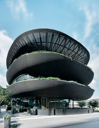 The building, designed by Collins and Turner, has a soft, organic form and is clad in linear dowels of charred timber.