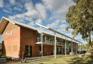 The new work is clearly articulated off the side of a 1960s red-brick building. A fly roof and colonnade encourage occupation of the outside space.
