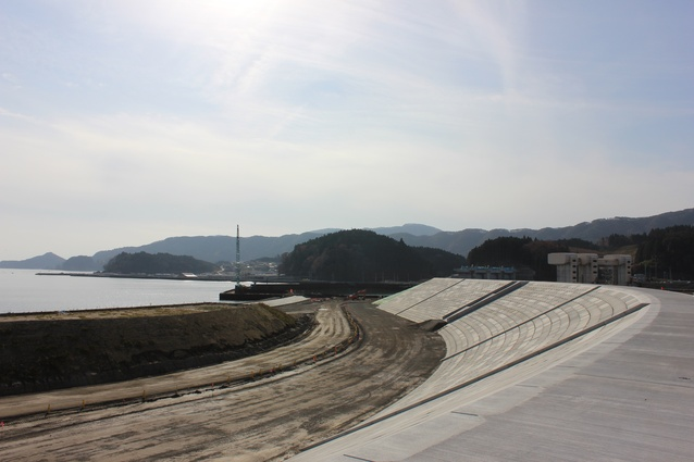 Seawall construction at Rikuzentakata looking toward the bay. The mound visible in the foreground is the site for future pine forest revegetation.