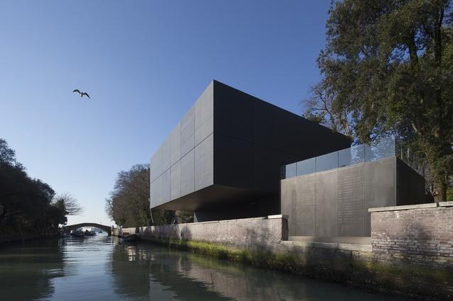 The pavilion's box-like form over a canal in the historic Giardini della Biennale.