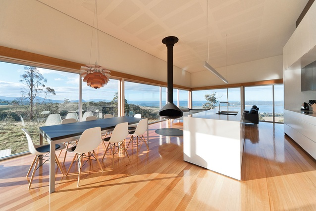 The kitchen and dining room are filled with light and focused towards views framed by glazing.
