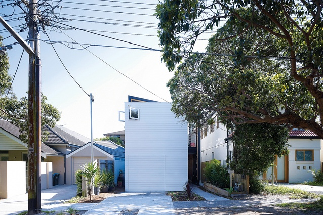 The facade presents as a simple white box, with only a hint at the house's unusual volumetric arrangement.