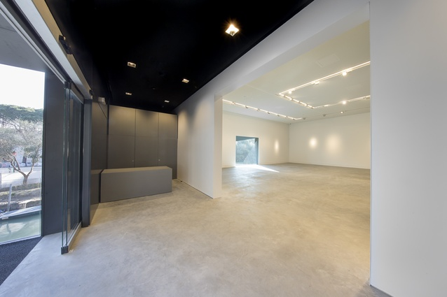 The lobby serves as an elegant link between the black exterior and bright white interior.