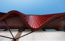 """Looking up at the fluid brise-soleil """"curtain"""" and pressed metal soffit."""
