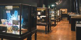 The exhibition installed at the Victoria and Albert Museum. A row of paired Victorian display cases stretching toward the end wall, on which Gregory Burgess Architects' model of the Brambuk Living Cultural Centre is displayed.