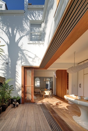The timber screens and battens cast playful shadows across the kitchen, blurring the boundaries between inside and out.