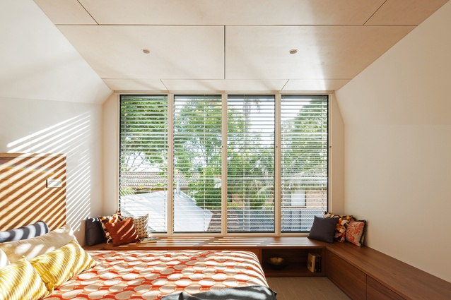 Bench seating under the window in the upstairs bedroom serves as storage and a well-lit reading spot.