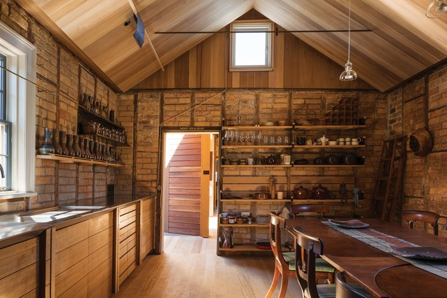 The original, once-detached kitchen volume has been reinstated as both a kitchen and dining room, where raw steel shelves of Wardle's design display his collection of carafes from Bendigo Pottery.