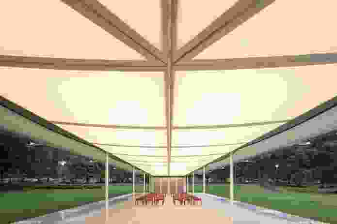 The fabric of Glenn Murcutt's 2019 MPavilion roof allows sunlight to shine through and is lit at night like a lantern.