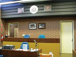 The bench of the Nadju–Norseman Community Court is unchanged (shown here before the community table). However, donated Aboriginal paintings and photographs now hang above it.