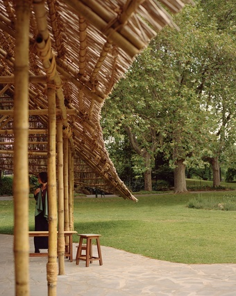 Opposite: The edges of the pavilion's roof spread beyond the supporting bamboo columns, forming an expansive canopy.
