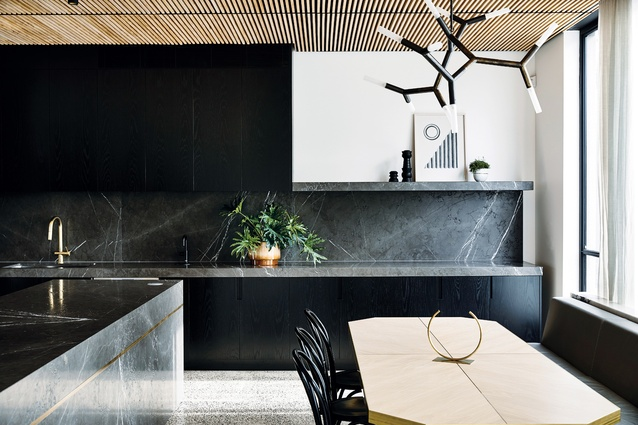 Dark, veined marble features heavily in the kitchen, and is carried through built-in joinery pieces. Artwork: Sean Meilak.