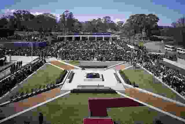对称的庭院由水平座椅、铺路和草地组成,通向纪念喷泉。