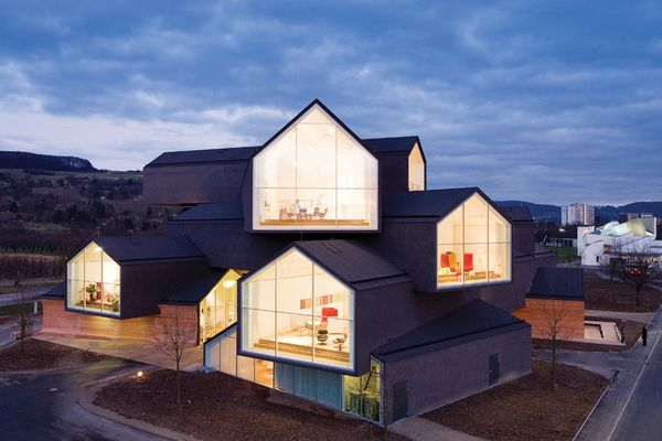 Elevated above the Vitra Campus in Germany, the building form is made up of a series of stacked, long, gabled roof telescopes.